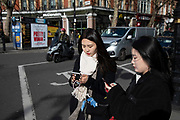 Two Chinese woman checking their smart phones on 18th February 2020 in London, England, United Kingdom.