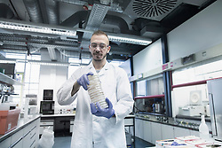 Scientist holding stack of petri dishes in a pharmacy laboratory, Freiburg im Breisgau, Baden-Wuerttemberg, Germany