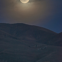 A Super Moon rises over the arid Inyo Mountains of eastern California