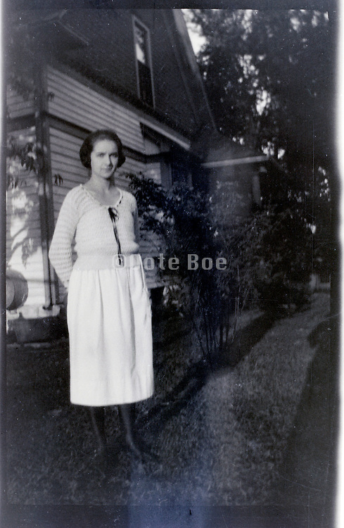 woman standing by house 1920s 1930s USA
