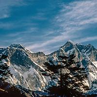 Mounts Everest and Lhotse tower behind pine trees near Tengboche Monastery in the Khumbu region of Nepal.