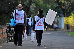 © Licensed to London News Pictures. 30/11/2011, London, UK. Two protesters from the Royal College of Nursing walk through a park. Up to two million public sector workers are staging a strike over pensions in what is set to be the biggest walkout for a generation. Photo credit : Stephen Simpson/LNP