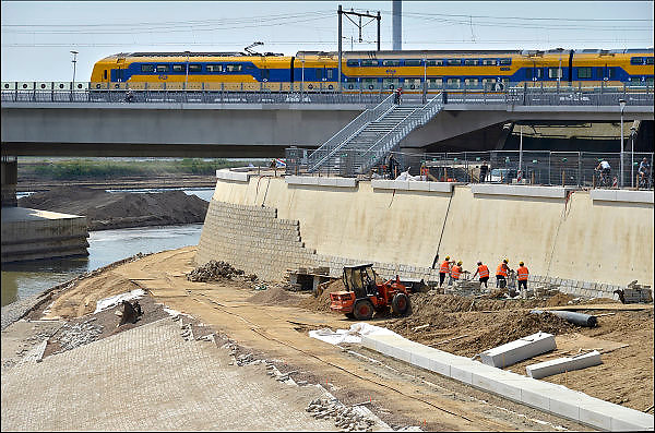 Nederland, Nijmegen, 25-6-2015 De nevengeul aan de overkant van de Waal bij Lent nadert zijn voltooiing. Grootste onderdeel van de vele werken van Rijkswaterstaat om bij hoogwater een betere waterafvoer in de rivier te hebben. Bij de nieuwe recreatiekade. Het is een omvangrijk project waarbij onder meer de pijlers van het spoorviaduct een bredere basis kregen omdat die straks in de loop van het water staan. Ook de n325 die vanaf de Waalbrug naar Arnhem loopt ist over 400 meter opnieuw worden aangelegd omdat het talud vervangen wordt door een nieuwe brug met drie gracieuze pijlers. De weg werd via een bypass omgeleid. Het dorp veurlent komt op een kunstmatig eiland te liggen met twee bruggen als ontsluiting. Een voetgangersbrug en een andere, de Promenadebrug, voor normaal verkeer. Inmiddels begint de nieuwe kade aan de noordkant van deze geul vorm te krijgen. Ruimte voor de rivier, water, waal. In de nieuwe dijk wordt een drempel gebouwd die stapsgewijs water doorlaat en bij hoogwater overloopt.Terwijl bouwvakkers bezig zijn met de bekleding van de betonnen kademuur rijdt een trein van de ns over de spoorbrug.The Netherlands, Nijmegen Measures taken by Nijmegen to give the river Waal, Rhine, more space to flow during highwater and to prevent the risk of flooding. Room for the river. Reducing the level, waterlevel. Large project to create a new paralel gully, an extra flow of water, so the river can drain more water during highwater. Due to climate change and expected rise, increase of the sealevel, the Dutch continue to protect their land from the water.Foto: Flip Franssen/Hollandse Hoogte