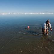 A native Inuit woman preparing nets for fishing for Arctic char. Barrow, Alaska