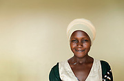 Portrait of local woman against wall, Musoto, Mbale, Uganda