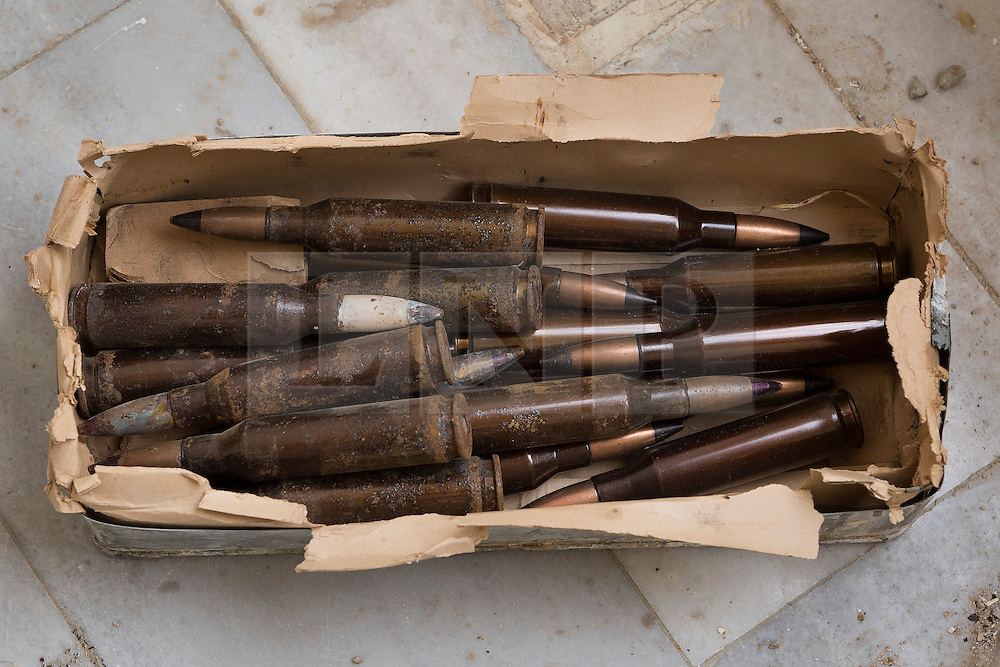 © Licensed to London News Pictures. 28/09/2014. Al-Yarubiyah, Syria. 12.7mm (.50 caliber) rounds, lie on the floor of a building in Al-Yarubiyah, Syria, as they wait to be used by Syrian-Kurdish YPG snipers firing at positions held by Islamic State insurgents in Rabia, Iraq.<br /> <br /> Facing each other across the Iraq-Syria border, the towns of Al-Yarubiyah, Syria, and Rabia, Iraq, were taken by Islamic State insurgents in August 2014. Since then The town of Al-Yarubiyah and parts of Rabia have been re-taken by fighters from the Syrian Kurdish YPG. At present the situation in the towns is static, but with large exchanges of sniper and heavy machine gun fire as well as mortars and rocket propelled grenades, recently occasional close quarter fighting has taken place as either side tests the defences of the other. Photo credit: Matt Cetti-Roberts/LNP
