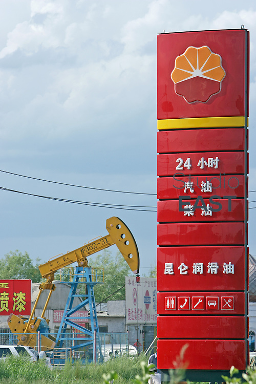 """HEILONGJIANG PROVINCE, CHINA - July 13: A Petrochina gas station waits for customer near a CNPC """"nodding donkey"""" oil pump on July 13, 2006 in Daqing, Heilongjiang province, China. China National Petroleum Corp. (CNPC) is the parent company of PetroChina. PetroChina went public on the Shanghai Stock Exchange Monday, Nov. 5, and the shares nearly tripled the same day. At US$1.005 trillion market capital, PetroChina is now the only trillion-dollar company in the world, twice the value of its US peer Exxon Mobil. (Photo by Servais Mont/Getty Images)"""