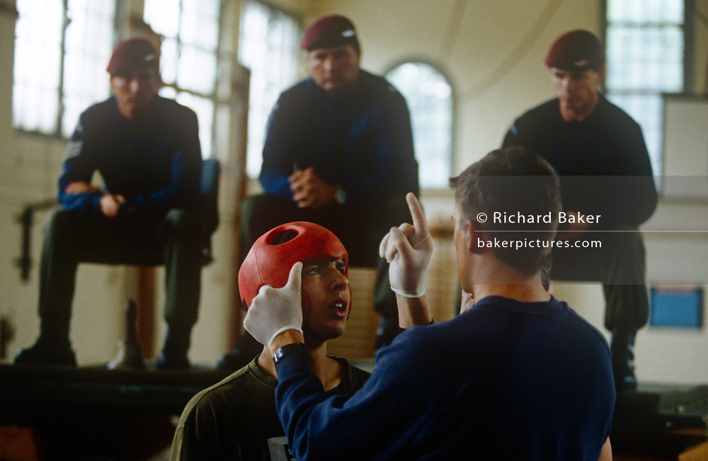 An physical education instructor tests an army recruit for concussion after a bout of Milling, a test of aggression that  recruits must pass before qualifying as a paratrooper in the Para Regiment of the British Army, on 23rd July 1996, at Aldershot, England. The controversial Milling tradition unique to the Paras is a test for young men to prove they have a killer spirit by a timed gloved one-to-one boxing fight. Within that time, they have to punch as fiercely as possible, often resulting in blooded noses and temporary concussion.