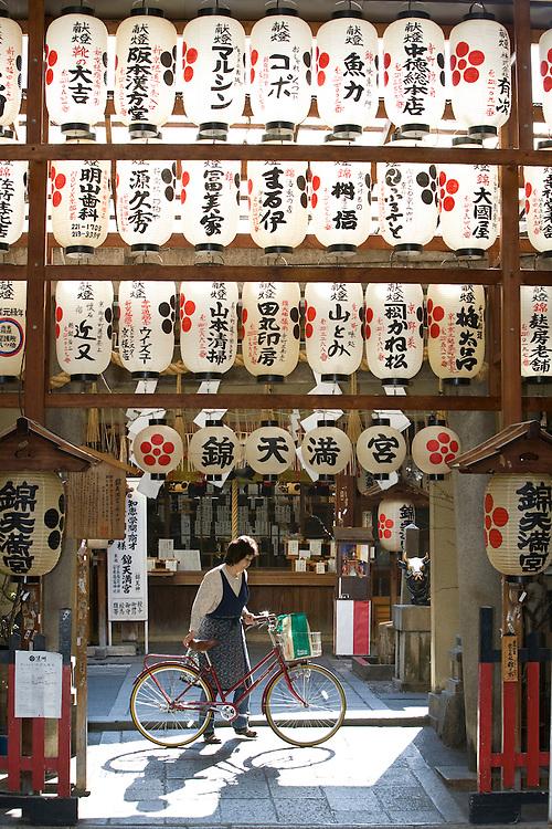 Asia, Japan, Honshu island, Kyoto, woman walks bicycle under paper lanterns at entrance to Nishiki Tenman-gu Shrine