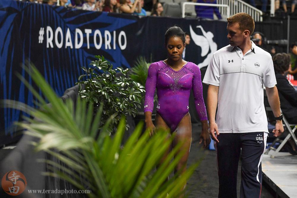 July 8, 2016; San Jose, CA, USA; Gabby Douglas (left), from Tarzana, CA, reacts with coach Christian Gallardo (right) after the balance beam in the women's gymnastics U.S. Olympic team trials at SAP Center.