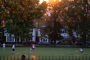 With a setting sun sinking below a line of homes and ash trees, a group of friends play a game of informal cricket in Ruskin Park, a public green space in Lambeth, south London, on 9th June 2021, in London, Englnd.