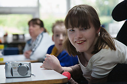 Physically disabled girl learning how to use a camera,