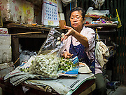 21 OCTOBER 2014 - BANGKOK, THAILAND: A worker in the Bangkok Flower Market makes a floral decoration used in religious ceremonies. The Bangkok Flower Market (Pak Klong Talad) is the biggest wholesale and retail fresh flower market in Bangkok. It is also one of the largest fresh fruit and produce markets in the city. The market is located in the old part of the city, south of Wat Po (Temple of the Reclining Buddha) and the Grand Palace.    PHOTO BY JACK KURTZ
