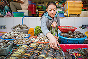 28 MARCH 2012 - HO CHI MINH CITY, VIETNAM:   A crab vendor in the Ben Thanh Market in Ho Chi Minh City, Vietnam. Ben Thanh Market is a large market in the downtown area of Ho Chi Minh City (Saigon), Vietnam in District 1. The market is one of the earliest surviving structures in Saigon and one of the city's landmarks, popular with tourists seeking local handicrafts, textiles,ao dais (Vietnamese traditional dresses), and souvenirs, as well as local cuisine. The market developed from informal markets created by early 17th century street vendors gathering together near the Saigon River. The market was formally established by the French colonial powers in 1859. This market was destroyed by fire in 1870 and rebuilt to become Saigon's largest market. In 1912 the market was moved to a new building and called the New Ben Thanh Market to distinguish over its predecessor. The building was renovated in 1985.     PHOTO BY JACK KURTZ