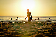 Early morning on a part of China beach in Danang. Silhouette of a man walking by the sea. Almost half of the picture is sand. People are playing in the water in the background. On top of the boy's head, the sun is shining.