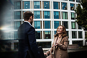 Business people talking outside corporate office buildings in the offshore finance and banking area of St Helier Jersey, CI