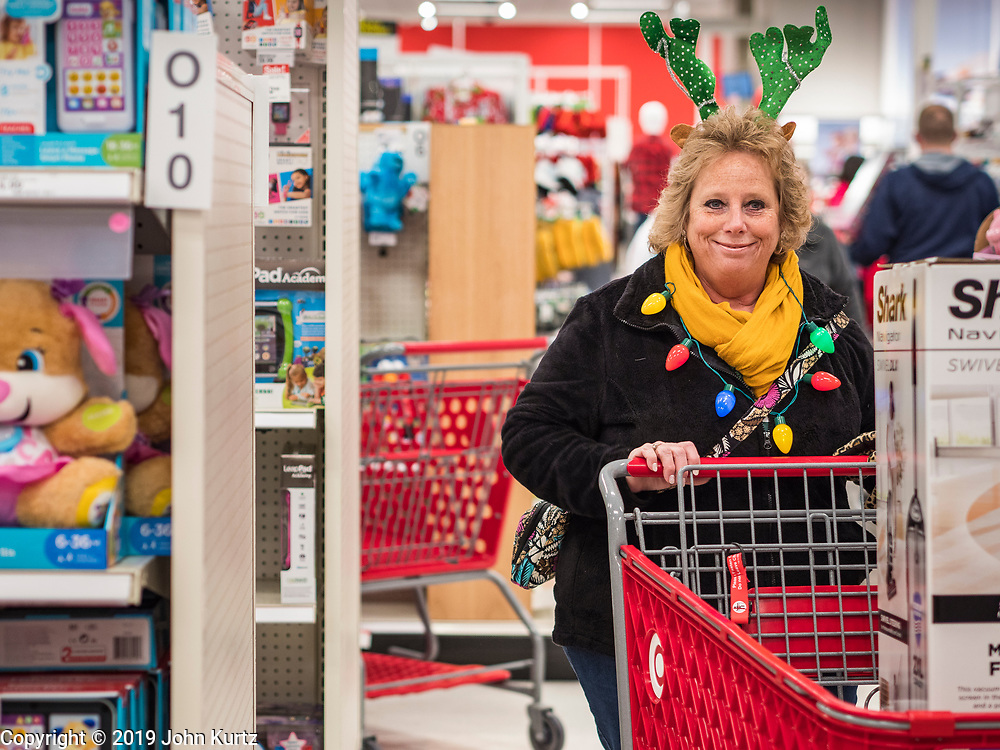 """28 NOVEMBER 2019 - ANKENY, IOWA: WANDA MORTVEDT, from Story county Iowa, wore a reindeer hat when she went shopping at the Target store in Ankeny, Iowa, Thursday. """"Black Friday"""" is the unofficial start of the Christmas holiday shopping season and has traditionally thought to be one of the busiest shopping days of the year. Brick and mortar retailers, like Target, are facing increased pressure from online retailers this year. Many retailers have started opening on Thanksgiving Day. Target stores across the country opened at 5PM on Thanksgiving to attract shoppers with early """"Black Friday"""" specials.     PHOTO BY JACK KURTZ"""