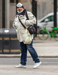 © Licensed to London News Pictures. 18/03/2020. London, UK. A man does his shopping in Victoria Street, Westminster as the majority of workers keep away from the centre of London as the Coronavirus pandemic crisis continues. Photo credit: Alex Lentati/LNP
