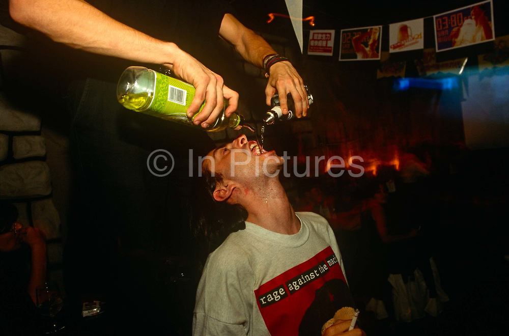 Foreign travellers and ex-pats play drinking games at a bar called CJ's in the Chinese economic region of Macau. An unseen person stands over the customer and pours a mixture of apparently lime and an alcoholic drink into the other man's open mouth. It spills and dribbles down his face but otherwise ends up in his throat for some kind of pleasurable – and expensive – youth experience. On his t-shirt are the words Rage Against the Machine, an anarchic message of rebellion.