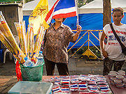 14 DECEMBER 2013 - BANGKOK, THAILAND:  People buy Thai flags and the yellow flag of the Thai monarchy on their way to an anti-government rally in Bangkok. The Thai anti-government movement, called the People's Democratic Reform Committee (PRDC) sponsored a forum Saturday to establish guidelines for political reform in Thailand. The opposition leader, Suther Thaugsuban, said his movement will not participate in a similar forum, sponsored by the government scheduled for Sunday. Thailand's political impasse continues with the opposition calling for the caretaker government of Prime Minister Yingluck Shinawatra to step down. Yingluck has, so far, refused to step down from her caretaker roll. Crowds at the anti-government rallies have shrunk substantially since the collapse of the government earlier in the week.       PHOTO BY JACK KURTZ