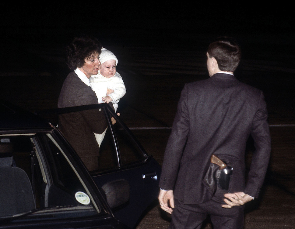 Prince William in the arms of his nanny Barbara Barnes and watched over by an armed police protection officer as they board a flight at Heathrow Airport,London bound for Australia. 1983. Photograph by Terry Fincher