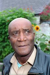 Older man in garden looking worried,
