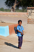 Boy in Hindu Brahman high caste village of Dhudaly heading for school in Rajasthan, Northern India