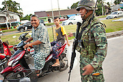 """Sept 26, 2009 -- PATTANI, THAILAND:  Thai soldiers man a checkpoint during a security operation near Krue Se Mosque in Pattani, Thailand Sept. 26. Thailand's three southern most provinces; Yala, Pattani and Narathiwat are often called """"restive"""" and a decades long Muslim insurgency has gained traction recently. Nearly 4,000 people have been killed since 2004. The three southern provinces are under emergency control and there are more than 60,000 Thai military, police and paramilitary militia forces trying to keep the peace battling insurgents who favor car bombs and assassination.   Photo by Jack Kurtz / ZUMA Press"""