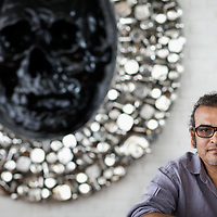 "Subodh Gupta, contemporary artist with one of his sculptures in his recently completed studio in Gurgaon, a satellite town of Delhi...Gupta's most celebrated sculptures are constructed from common domestic items including the steel pots and pans that are a feature every Indian home. Of the kitchen-ware that forms the basis of his work, Gupta says,..""The poor, the middle class and the rich use it at home. In this country, how many people have the utensils but they starve because there is no food?""..Gupta was brought up, one of six children, to a railway-worker father in a north Indian village. ..Gupta's work fetches such huge sums of money. Two versions of his Mind Shut Down, modeled on the human skull and constructed entirely of steel kitchen utensils recently sold for EUR1 million each...Photo: Tom Pietrasik.Gurgaon, Haryana. India. .June 26th 2009"