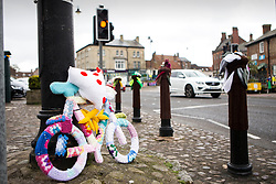 © Licensed to London News Pictures. 27/04/2016. Thirsk UK. Picture shows  a knitted bike in Thirsk that has been Yarn Bombed. Under the cover of Darkness 300 Yarn bombing street artist's have covered the Town centre of Thirsk, the group has covered bollards, flower pots, the bus stop, tree's, benches, even the local police station. The knitted creations took over 750 balls of wool & have been placed along the route of the Tour De Yorkshire which will pass through the town during it's final stage from Middlesborough to Scarborough on Sunday.  Photo credit: Andrew McCaren/LNP