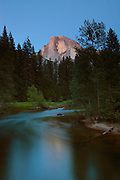 Half Dome, turned red by the twilight glow, towers over the Merced River in Yosemite National Park, California. Half Dome, 8836 feet (2693 meters) tall, is a granite dome that seems to be missing a large section. While named Half Dome, the missing piece is likely a quarter, rather than half. Scientists believe the missing granite also eroded away as fast as it was exposed, rather than falling off in a dramatic event.