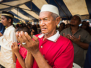 14 JUNE 2015 - NARATHIWAT, NARATHIWAT, THAILAND: Thai Muslims pray before a food distribution event in Narathiwat. The food distribution is held before Ramadan, which starts June 18. The annual food distribution event is organized by the Southern Peace Media Club, a group of Thai journalists who work in the southern provinces of Pattani, Narathiwat and Yala. An insurgency pitting Muslim extremists against the Thai government has rocked Thailand's southern three provinces since 2001. More than 6,000 people have been killed in the sectarian violence.    PHOTO BY JACK KURTZ