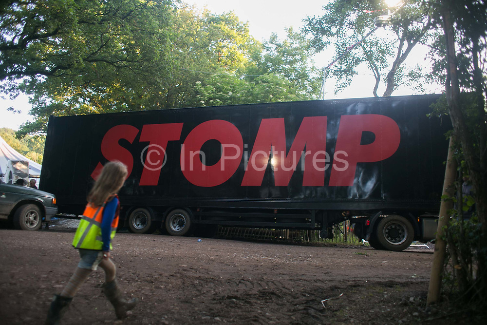 A child looks on as a large Stomp theater truck off-load 18th of June 2016 at Glastonbury Festival, Somerset, United Kingdom. Work getting the festival ready takes weeks and in the days up to the festival starts work is frantic.  The Glastonbury Festival runs over 3 days and has 3000 acts, including music, art and performance and approx. 150.000 attend the anual event.