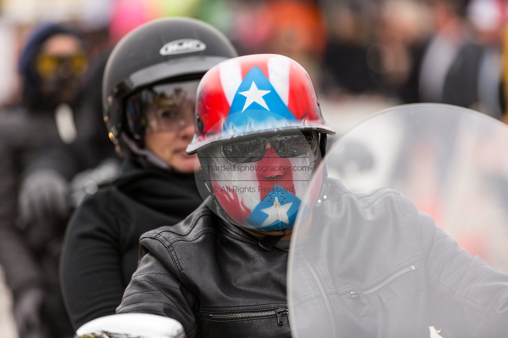 A biker wearing a red, white & blue helmet and mask cruises down Main Street during the 74th Annual Daytona Bike Week March 7, 2015 in Daytona Beach, Florida.