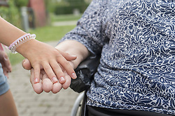 Granddaughter holding grandmother's hand on wheelchair at rest home park, Bavaria, Germany