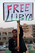 A holds up a sign for a free Libya in  the main square of Tabrurk where people are demanding Qadaffi to leave on Feb. 24, 2011. The square has become a symbol of New Libya, tents have been set up, people are giving out free food, and heavy equiptment is being used to repair the square.