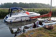 The wash from a passing Norfolk Broads pleasure cruiser disturbs the peace for man enjoying the tranquility while fishing for perch on the still waters of the river Chet, on 13th August 2020, in Loddon, Norfolk, England.