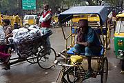 Ravi Hazara, 40, a rickshaw puller in Old Delhi  waiting for a job outside a motor part shop that often employs him. India