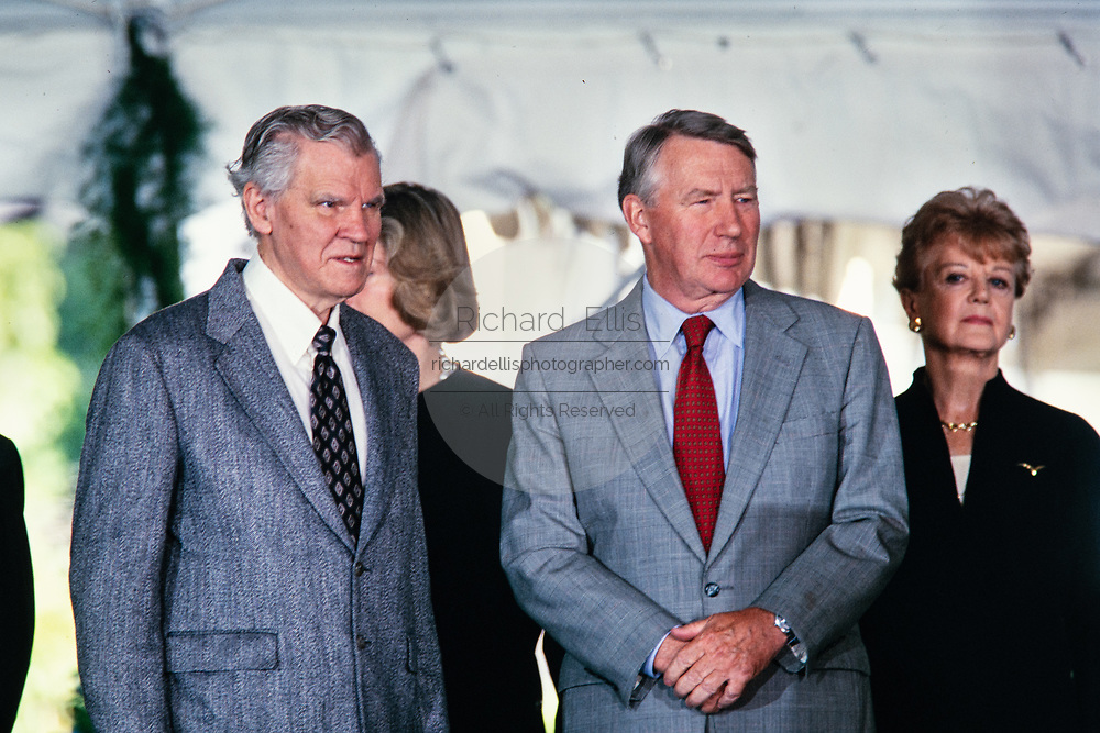 Journalist Robert MacNeil, center, stands with musician Doc Watson, left, and actress Angela Lansbury, right, during the National Medal of Arts and Humanities awards during a ceremony on the South Lawn of the White House September 29, 1997 in Washington, DC.