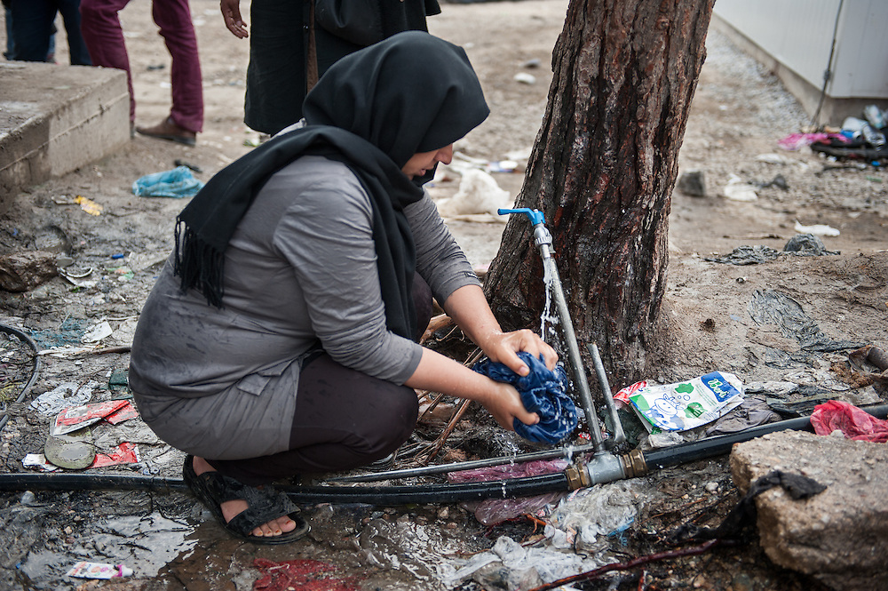 A woman washes clothes at a water tap in Moria camp , Lesvos, Greece.