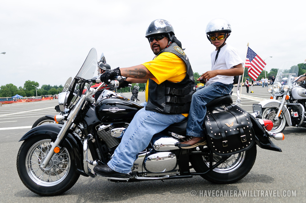 A rider and child participating in the annual Rolling Thunder motorcycle rally through downtown Washington DC on May 29, 2011. This shot was taken as the riders were leaving the staging area in the Pentagon's north parking lot, where thousands of bikes and riders had gathered.