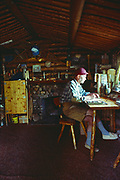 Dick Proenneke writing in journal at desk in his cabin, Upper Twin Lake, Lake Clark National Park, Alaska.