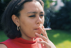 Young woman standing outdoors smoking a cigarette,