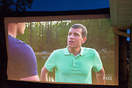 """Merrick, New York, USA. 11th June 2017.  On large TV screen, """"American Grit"""" TV show contestant CHRIS EDOM (at right), 48, of Merrick, is host of Viewing Party for Season 2 premiere. Edom family's neighbors watched Episode 1 of the Fox network TV reality show on large screen in their backyard. Edom was the last contestant picked for a team."""