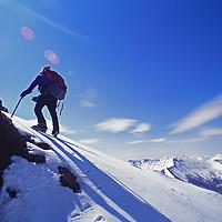 A mountaineer ascends slope below Pilot Peak.
