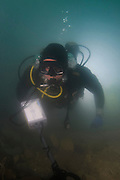 Underwater survey. Scuba diver uses a metal detector to help search for buried objects. In this case a hoard of 2000 gold coins were found in Caesarea Harbour, Israel