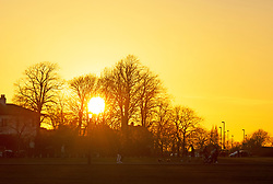 © Licensed to London News Pictures 26/02/2021.        Blackheath, UK. The sun setting over the Common. People get out of their homes from a third national Coronavirus lockdown to enjoy some bright sunny weather on Blackheath Common, London. Photo credit:Grant Falvey/LNP