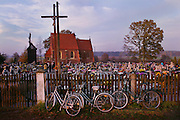 Stradomia Wierzchnia village, Poland. Cemetery with church and bicycles against fence on All Saints Day.