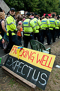 Balcombe, West Sussex. Site of Cuadrilla drilling. Demonstration against fracking 18.08.2013. A line of police walk alongside the demonstration and past a sign saying 'Fracking well expect us'.