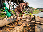 16 SEPTEMBER 2014 - SANGKHLA BURI, KANCHANABURI, THAILAND: A member of the Mon community cuts a pylon to fit the repaired Mon Bridge in Sangkhla Buri. The 2800 foot long (850 meters) Saphan Mon (Mon Bridge) spans the Song Kalia River. It is reportedly second longest wooden bridge in the world. The bridge was severely damaged during heavy rainfall in July 2013 when its 230 foot middle section  (70 meters) collapsed during flooding. Officially known as Uttamanusorn Bridge, the bridge has been used by people in Sangkhla Buri (also known as Sangkhlaburi) for 20 years. The bridge was was conceived by Luang Pho Uttama, the late abbot of of Wat Wang Wiwekaram, and was built by hand by Mon refugees from Myanmar (then Burma). The wooden bridge is one of the leading tourist attractions in Kanchanaburi province. The loss of the bridge has hurt the economy of the Mon community opposite Sangkhla Buri. The repair has taken far longer than expected. Thai Prime Minister General Prayuth Chan-ocha ordered an engineer unit of the Royal Thai Army to help the local Mon population repair the bridge. Local people said they hope the bridge is repaired by the end November, which is when the tourist season starts.    PHOTO BY JACK KURTZ